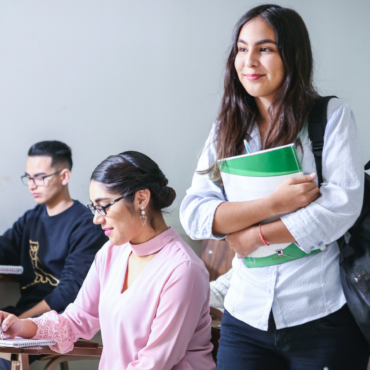 A woman with long dark hair holding books and wearing a backpack standing while surrounded by students sitting in a classroom