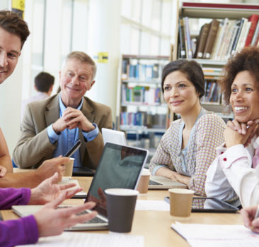 A group of 6 people sitting around a table in a library having a meeting