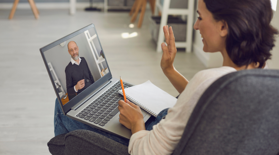 Two people speaking through Video Chat on a Laptop