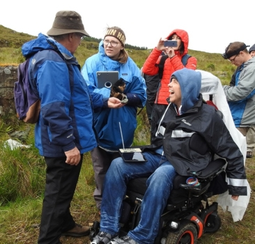 Faculty and students participating in a field science program. A faculty member holds out a rock. A student in a wheelchair smiles while conversing with the faculty member.