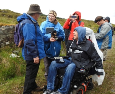 Faculty and students participation in a field science program. A faculty member holds out a rock. A student in a wheelchair smiles while conversing with the faculty member.