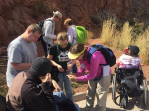Educators and students gather around to inspect a rock. A student in a wheelchair takes a picture of an exposed rock wall.
