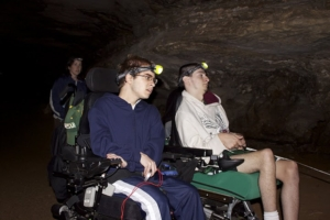 Two students in wheelchairs wear headlamps and explore a dark cave.