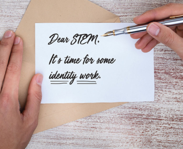 One hand presses a postcard against an open envelope, while another hand pens the message: