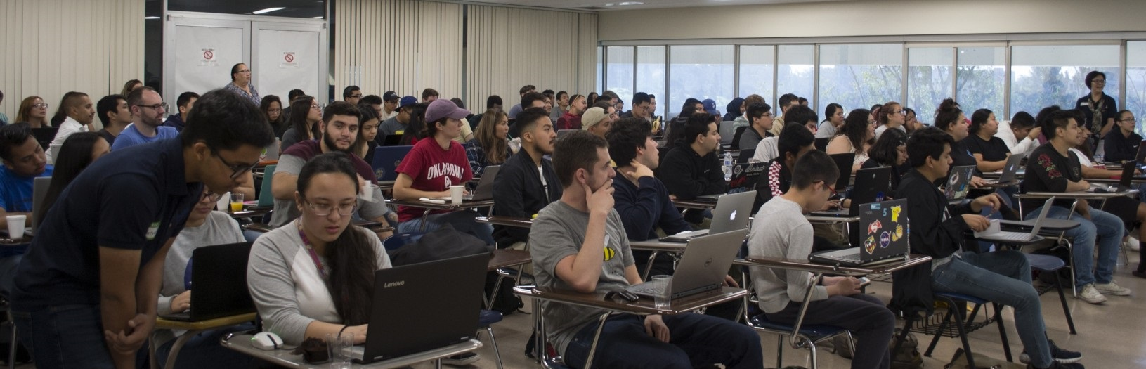 A large classroom of diverse students look towards the front of the room as they participate in Dr. Ye's summer workshop program.