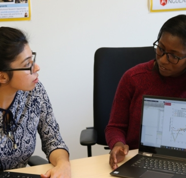 Two students sit side by side, displaying their computer towards each other to show a line graph and a map of the world.