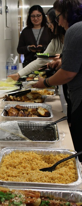 Eager students line up to enjoy trays of rice, beans, and chicken.
